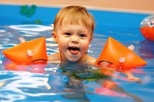 ребенок купается в бассейне